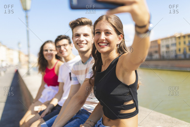 Italy- Pisa- group of four happy friends sitting on a wall along Arno river taking a selfie