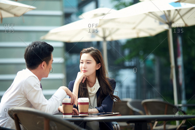 Young couples in outdoor drinking coffee