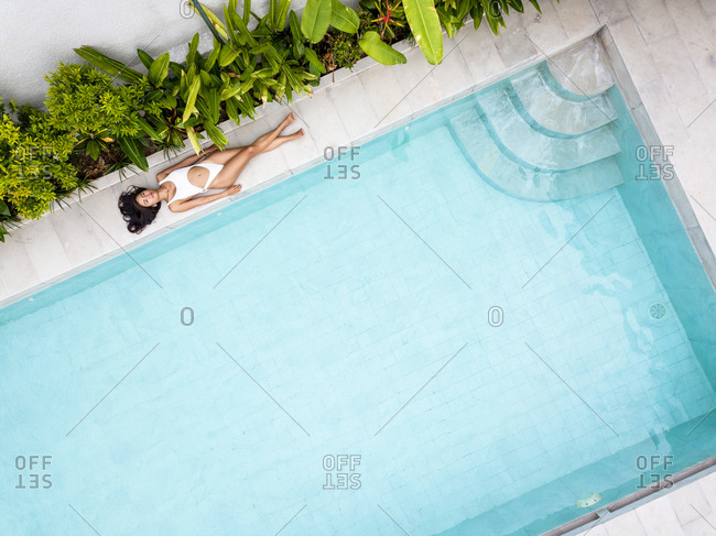 Aerial view of  Asiatic woman sunbathing on a white swimsuit on a pool