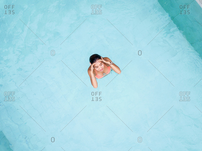 Aerial view of asiatic woman on a swimming pool
