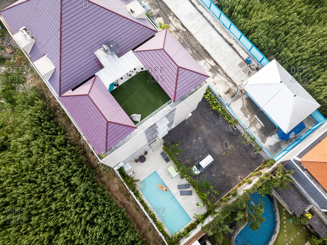 Aerial view of asiatic woman relaxing on an orange inflatable on a swimming pool