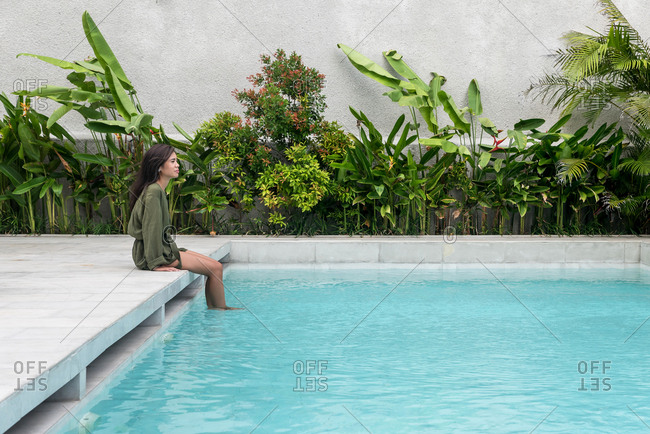 Asiatic woman sitting in front of a swimming pool
