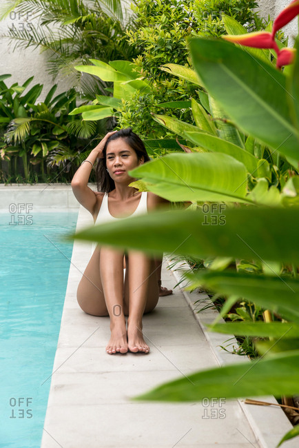 Asiatic woman sunbathing on a white swimsuit on a pool