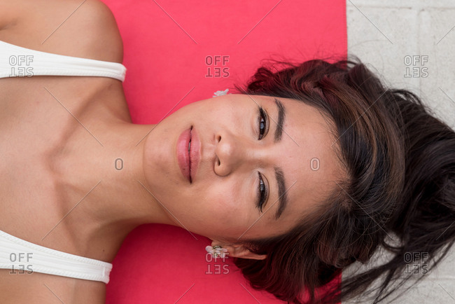 Asiatic woman sunbathing on a swimming pool