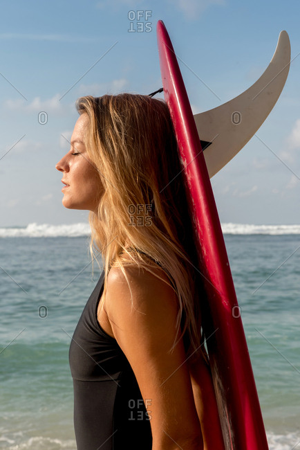 Surfer carrying surfboard on beach, Uluwatu, Bali