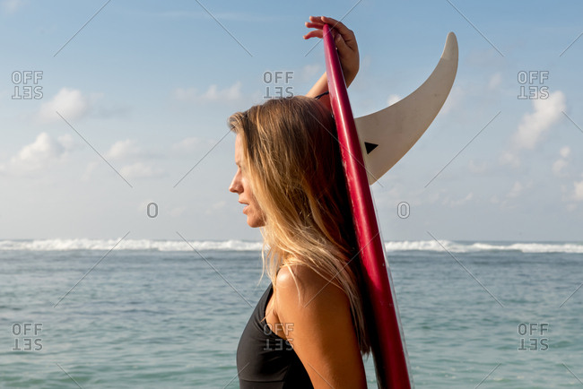 Surfer carrying surfboard on beach, Uluwatu, Bali