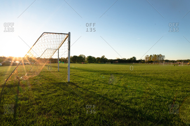 Soccer goal on field at sunset