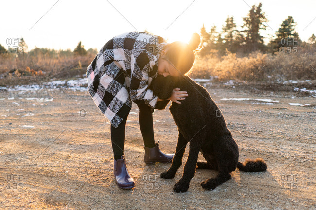 Girl hugging poodle at sunset