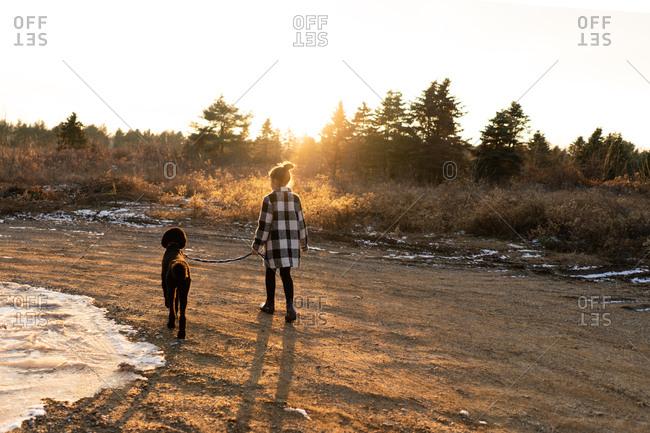 Girl walking poodle at sunset