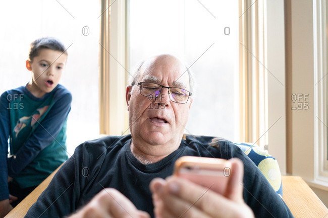 Boy watching over grandfather's shoulder while he uses Smartphone
