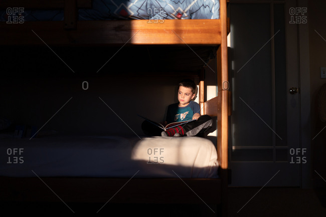 Boy reading book on bunk bed