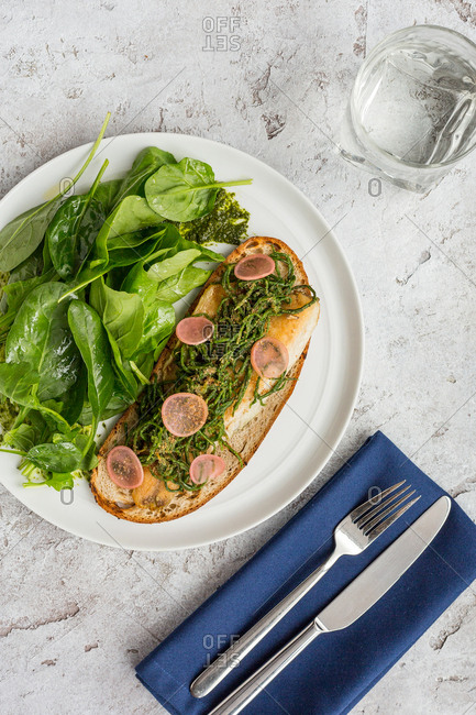Grilled fish and bread with fresh rocket