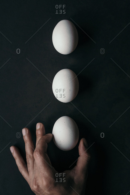 Three eggs and hand on the dark surface