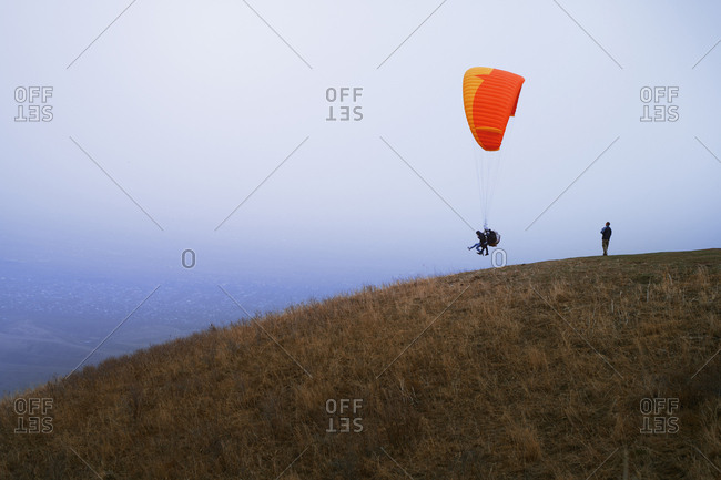 People learning to paragliding with trainer