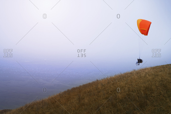 Skydiving on para-glider over the hill