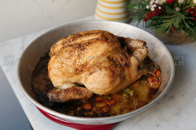 Whole roasted chicken cooked with vegetables in a serving dish