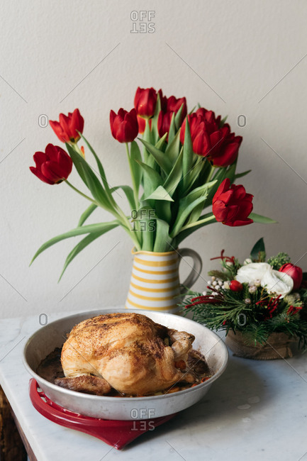 Roasted chicken on a table with flower arrangements