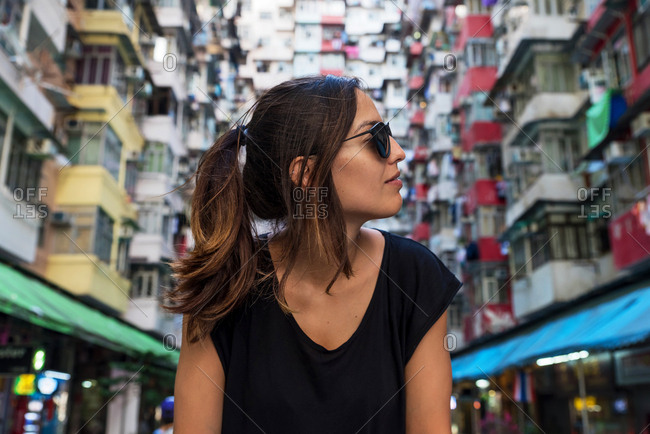 Woman in front of high-rise building with many units in Hong Kong