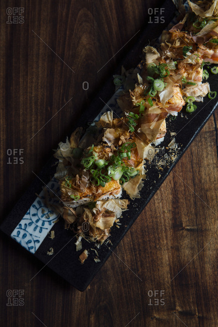 Sushi roll garnished with bonito flakes and scallions
