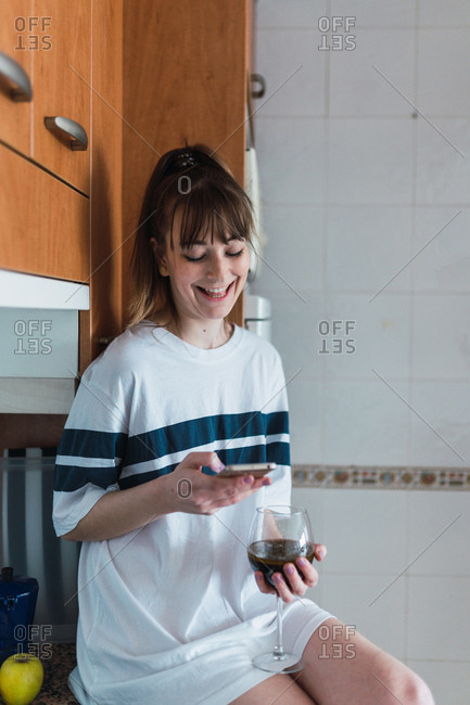 Beautiful young female with glass of red wine laughing and browsing smartphone while sitting near cupboards in kitchen