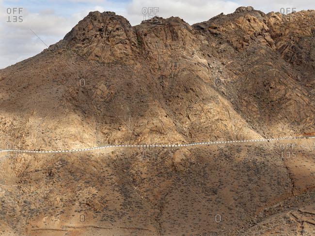 Pretty white fence on side of winding asphalt road on slope on wonderful hill on Fuerteventura Island, Spain