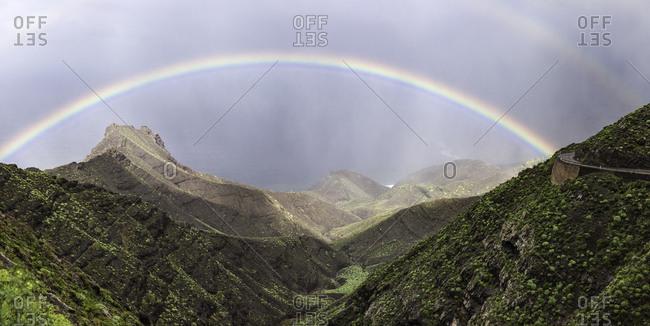 Vivid rainbow on cloudy sky over majestic mountain ridge on Gran Canaria Island, Spain