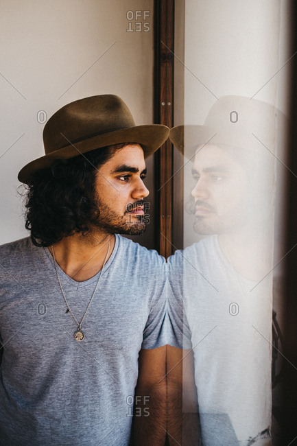 Adult modern man with curly hair and beard wearing hat and looking pensively in window
