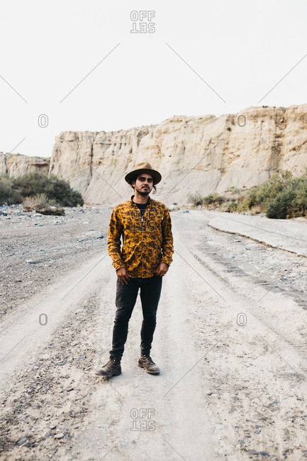 man in hat walking alone on rocky road in canyon