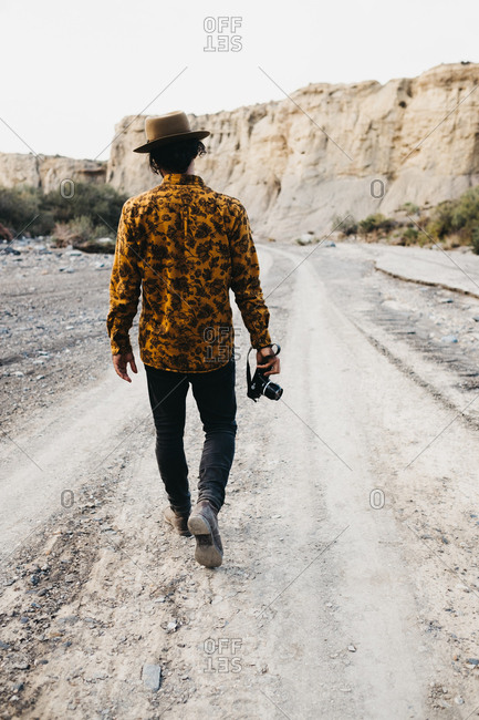 Back view of man in hat walking alone on rocky road in canyon carrying photo camera