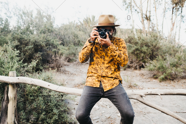 Contemporary stylish man in shirt and hat sitting on wood fence and taking picture with photo camera