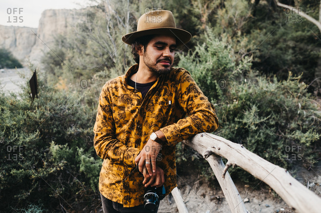 Contemporary stylish man in shirt and hat sitting on wood fence