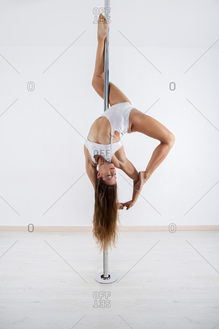 Beautiful barefoot female performing difficult dance movement on metal pole in studio