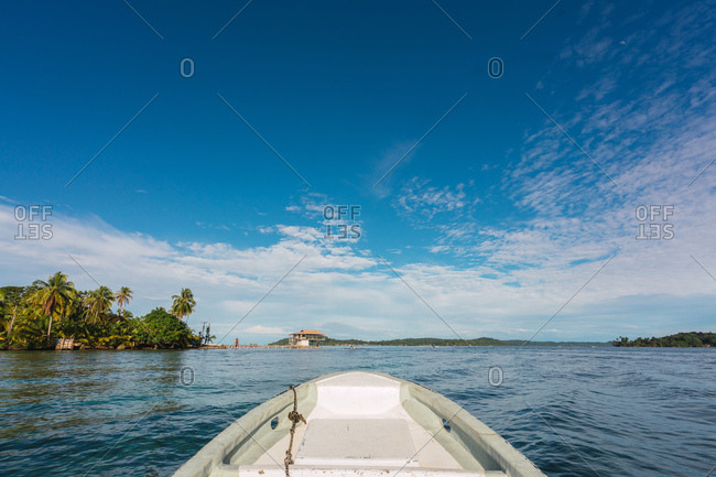 View of white boat beak sailing in calm water of blue water with exotic seashore in sunlight, Panama