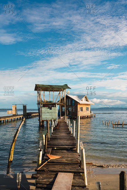 View of old wooden pier with small house in blue water of seascape, Panama