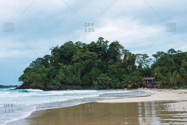 Picturesque view of tropical seashore beach with green palms and blue sky, Panama