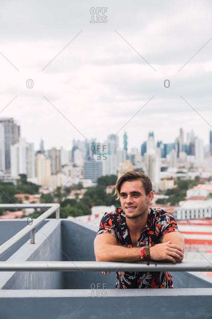 Handsome young guy smiling and looking away while leaning on terrace railing on background of modern city on cloudy day