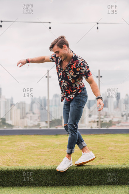 Handsome young male in stylish outfit smiling while walking on artificial grass of terrace on cloudy day in modern city