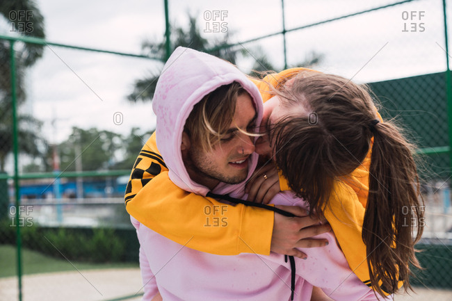 Handsome young guy laughing and giving piggyback ride to excited girlfriend while spending time on sports ground together