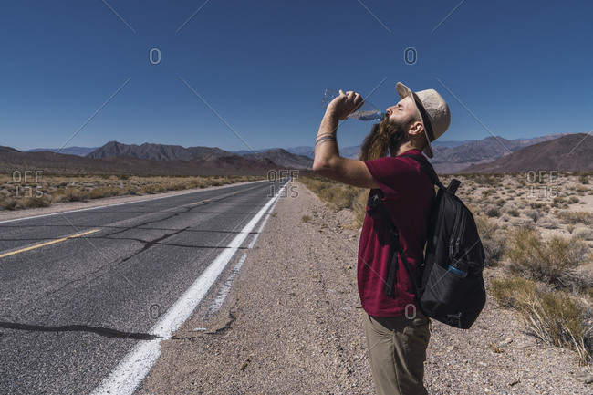 Side view young beard male in hat with backpack drinking water from bottle near route between field and hills