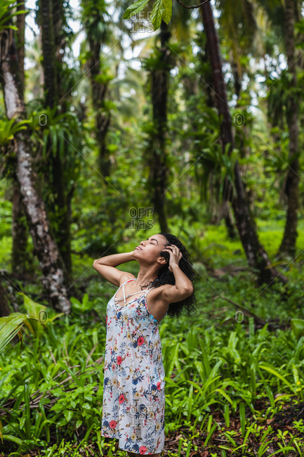 Attractive Hispanic woman with upping head and hands on hairs in green forest in Bocas del Toro Islands, Panama