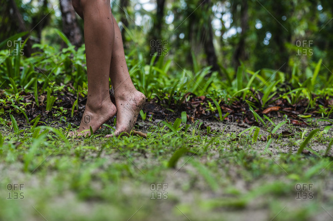 Side view of crop legs of barefooted woman on land in green forest in Bocas del Toro Islands, Panama