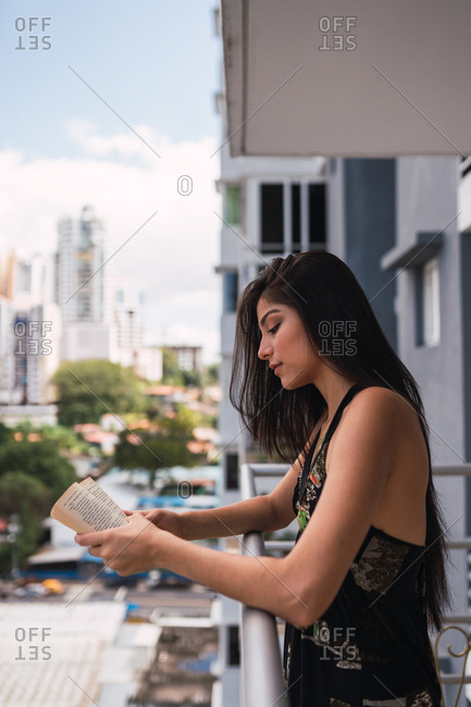 Beautiful passionate brunette woman in dress volume on balcony near modern buildings
