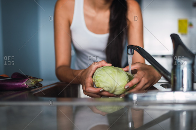 Beautiful passionate brunette Hispanic woman washing cabbage in sink near carrot, eggplants and cup in modern kitchen