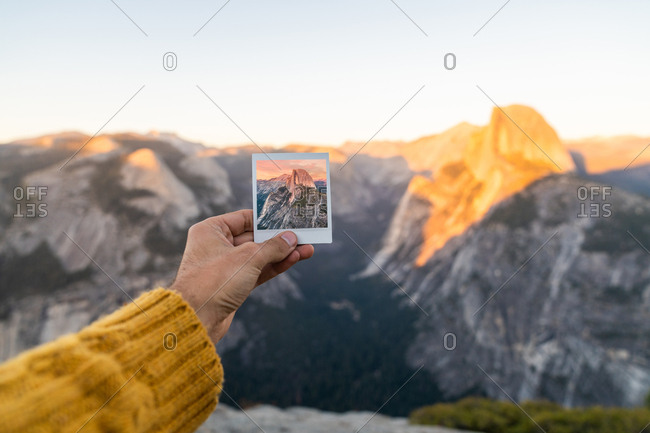 Crop hand of human holding shot and picturesque view of mountains at sunrise in Yosemite