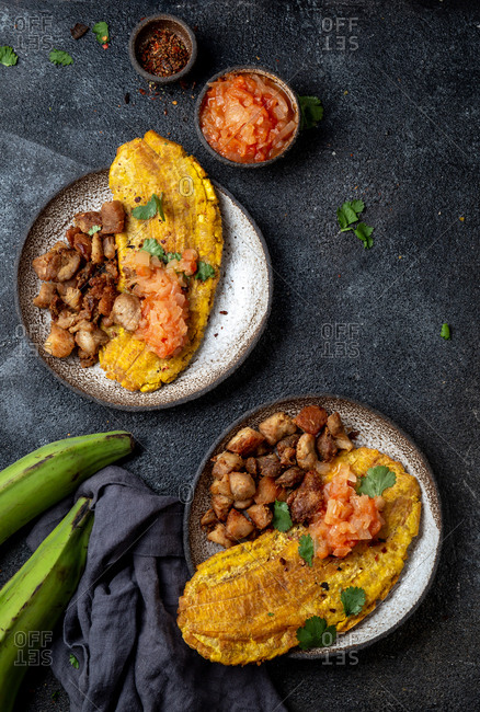 Top view of Central American dish patacon or toston fried green plantain with chicharron and tomato sauce