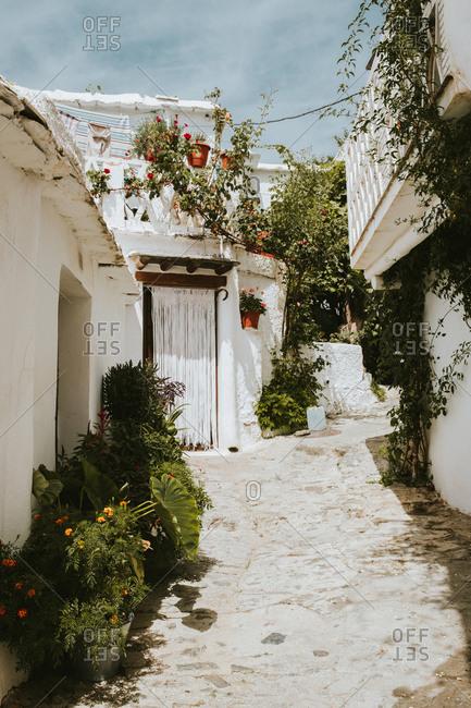 narrow city street amidst small houses on sunny day in Granada, Spain
