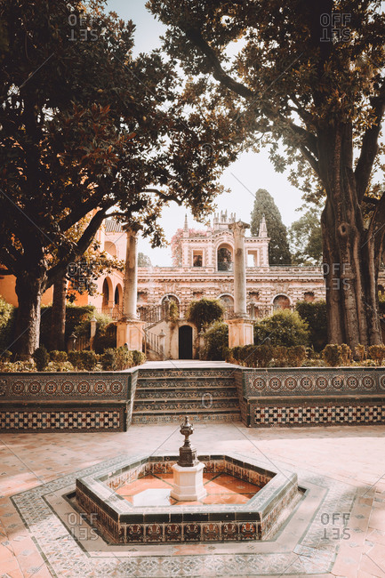 December 28, 2018: Beautiful small fountain located in yard of beautiful palace in Seville, Spain