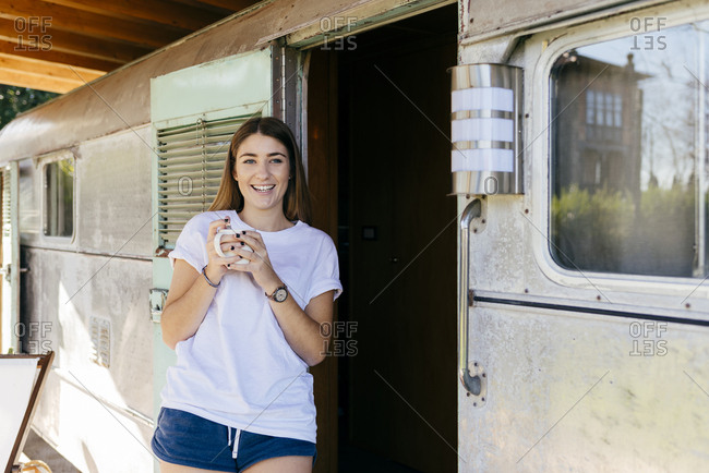 Pretty young lady with mug of hot beverage smiling and looking away while leaning on shabby camper in countryside