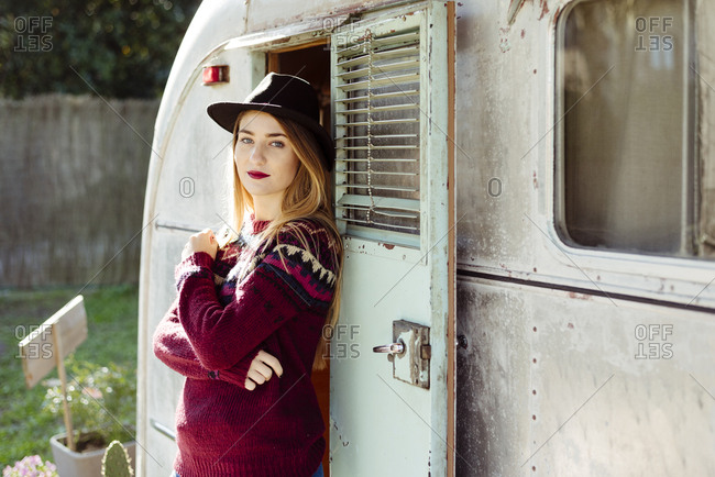 Beautiful young female in trendy hat and sweater keeping arms crossed and looking at the camera while standing near entrance of old camper