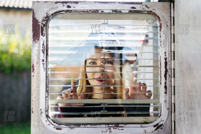 Pretty young lady looking at camera while standing behind grungy door of old caravan